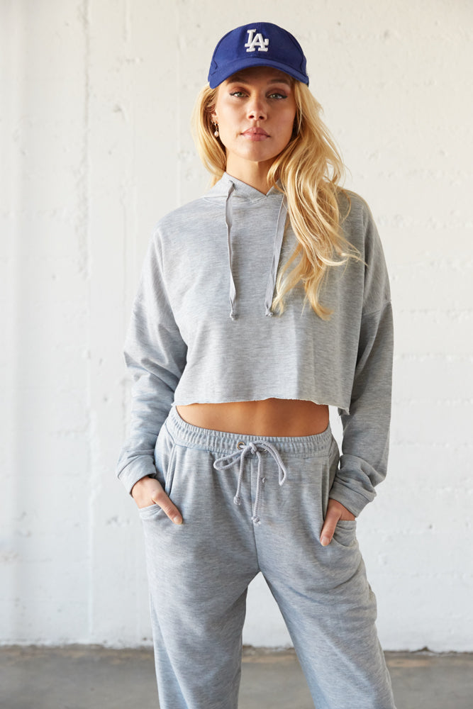 Grey cropped hoodie with drawstring tie.