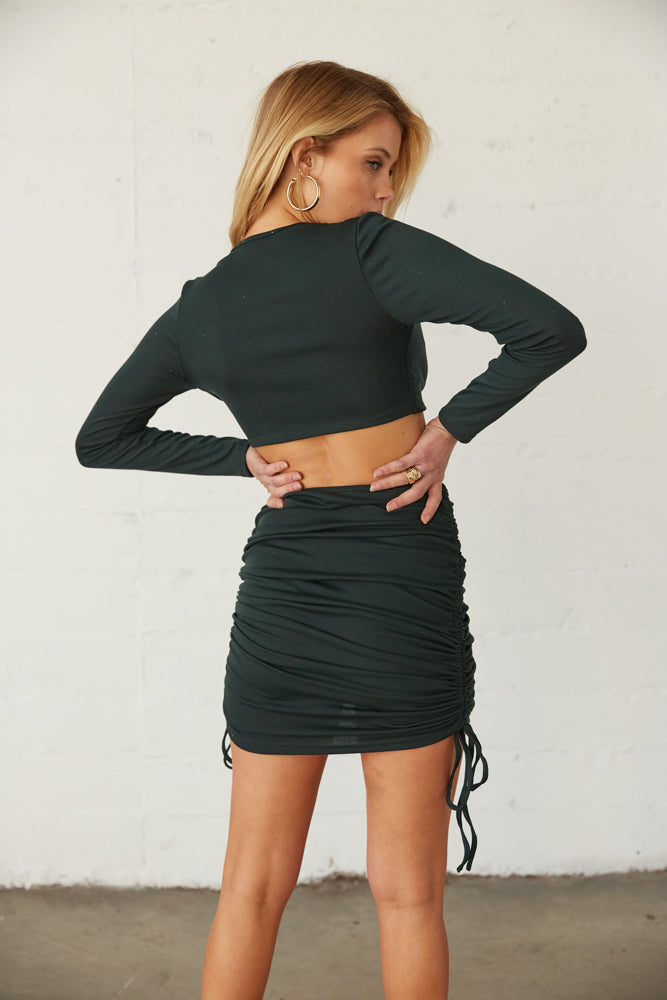 The back of the skirt is ruched and the top is extra cropped.