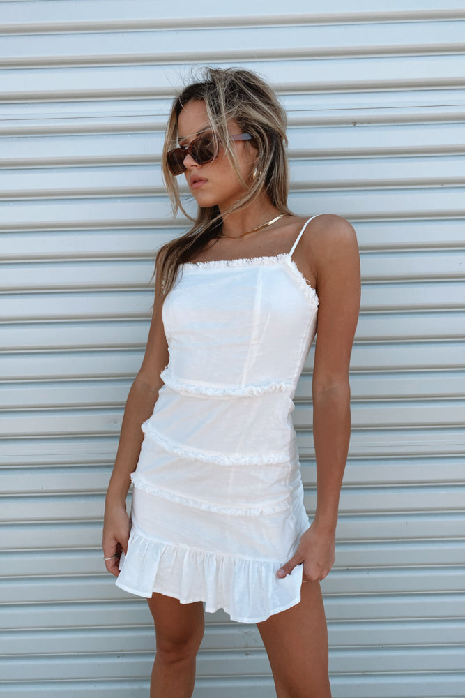 White mini dress with frayed detailing and a ruffle trim.