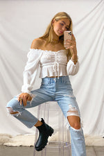 White smocked ruffle crop top with long sleeves.