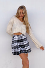 The side of the pleated tennis skirt has a black and white plaid design.