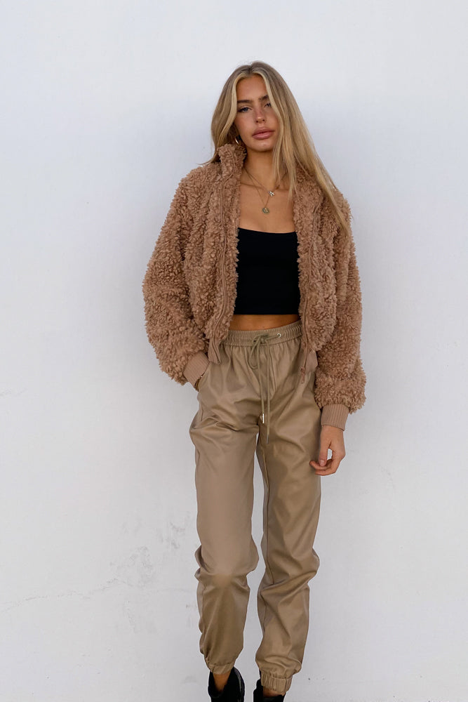 Cropped fuzzy jacket with tan leather joggers.
