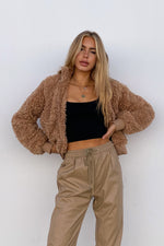 Brown teddy jacket with black tank top.