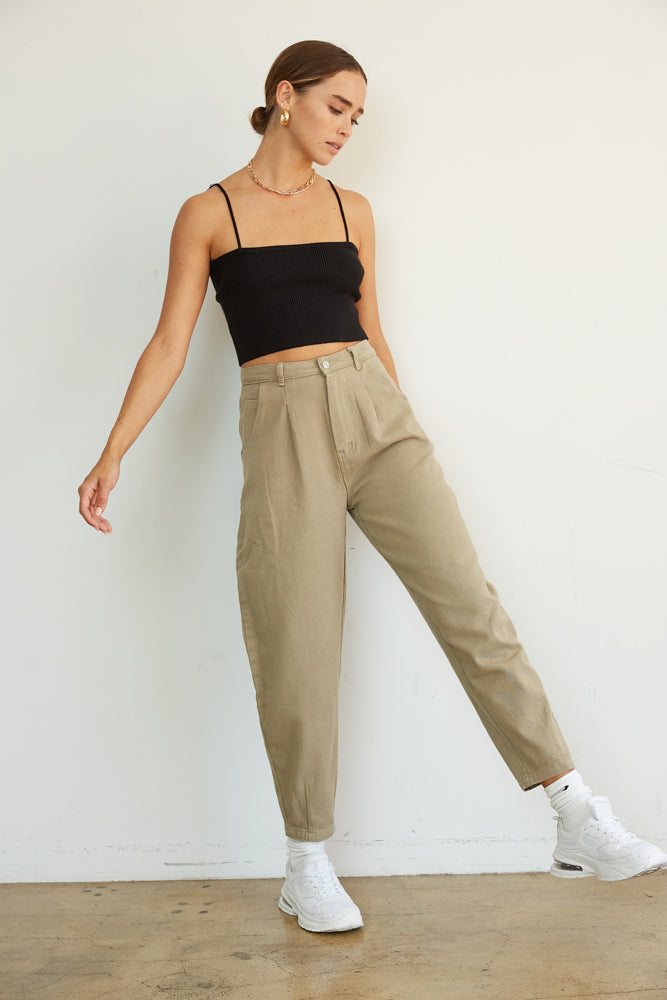Light olive trousers with pleated detailing.