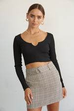 Belted plaid mini skirt with black top.