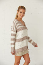 Distressed hem striped knit sweater.
