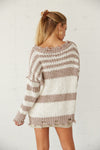 The back of this sweater is oversized with a distressed hem.