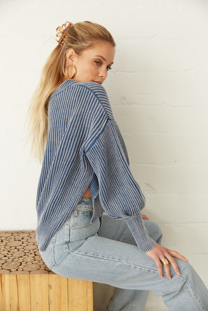 The side of this sweater has slits and long ribbed sleeves.