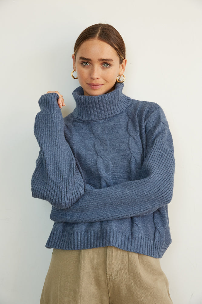 Navy cable knit turtleneck sweater.