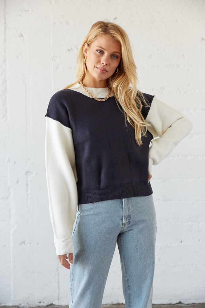 The sweater has a navy body and white sleeves and neckline.