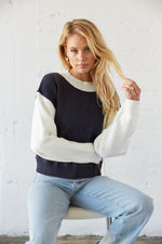 Navy and white colorblock knit sweater with exposed seams.