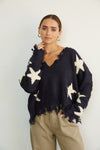 Navy and white distressed sweater with star print.