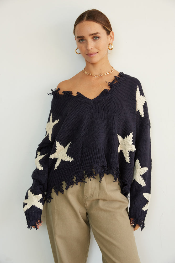 V neck sweater with distressed detailing and star print.