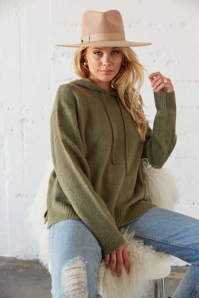 Slouchy green sweater with long sleeves.
