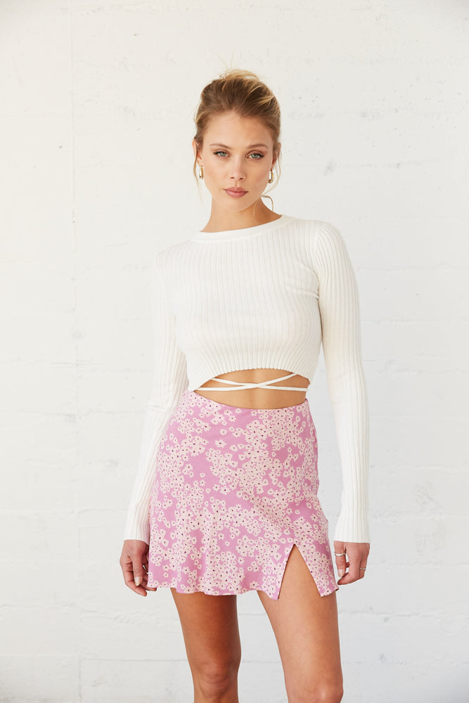 Pink floral mini skirt with side slit detail.
