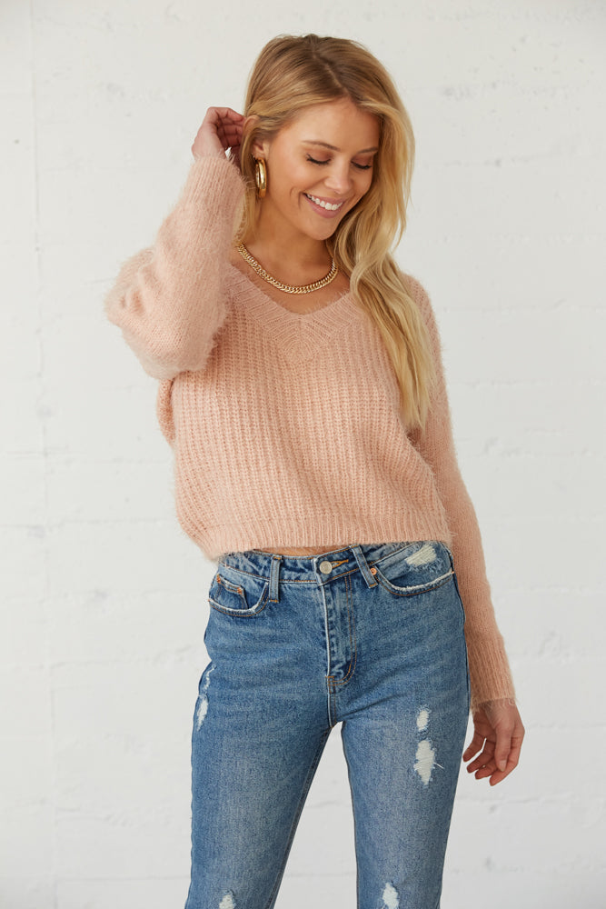 Cropped fuzzy sweater in pink.