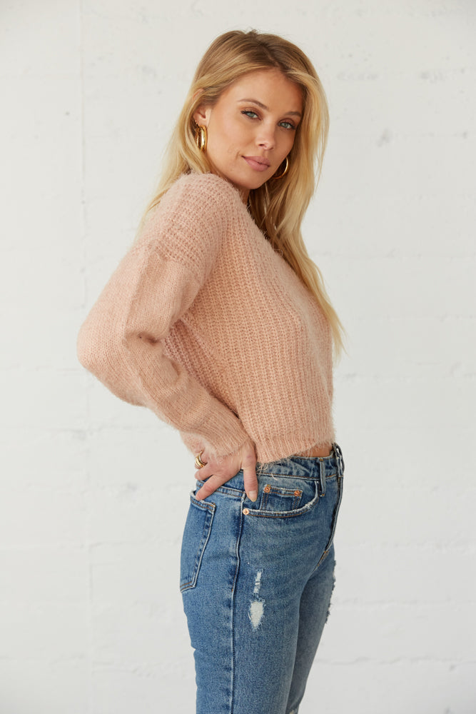 The side of this sweater has long sleeves and a cropped fit.