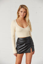 Beige ribbed crop top with black mini skirt.