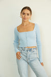 Blue ribbed crop top with square neckline and pearl buttons.