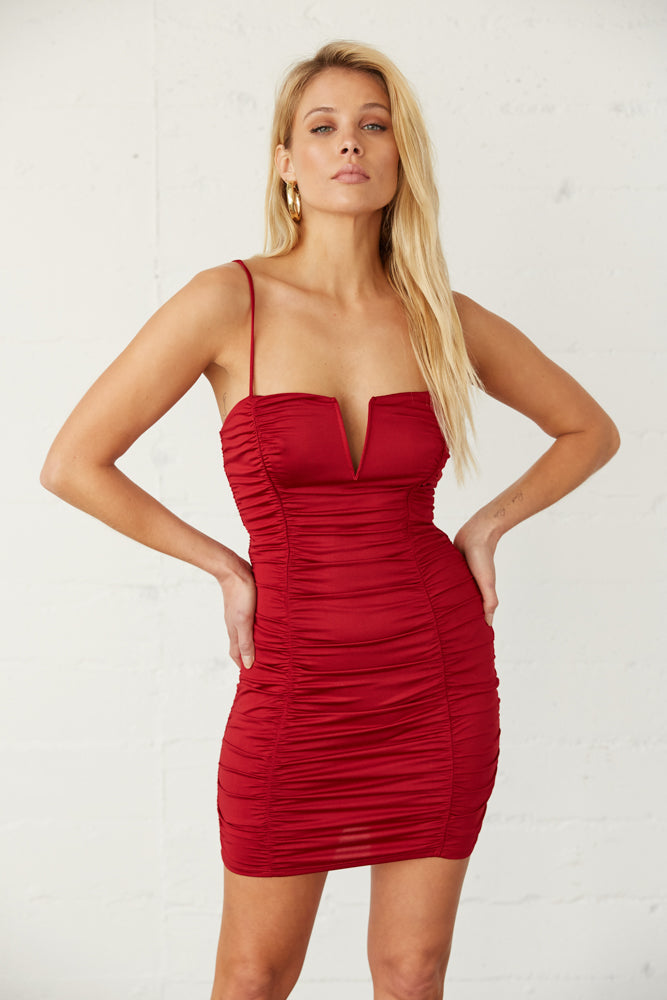 Red mini dress with ruched body and spaghetti straps.