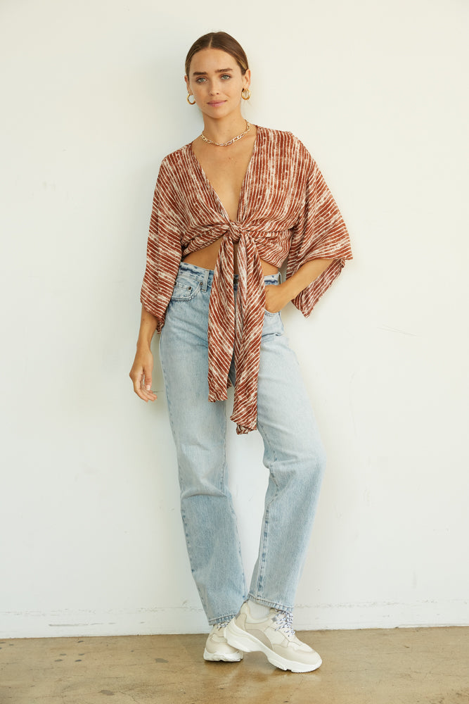 Rust and white printed striped wrap top.