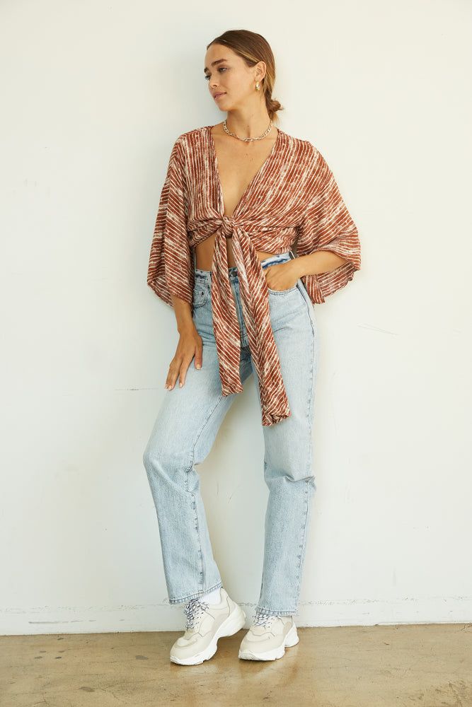 This flowy crop top has a front tie detail and a rust and white striped print.