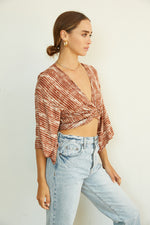 This top can be twisted in the front and tied in the back for a cropped fit.