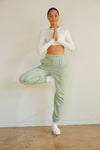Sage green sweatpants with a baggy fit.