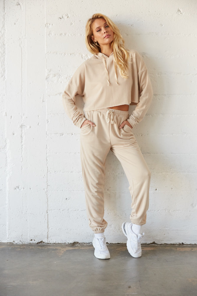 Tan sweatshirt with long sleeves and a raw hem.