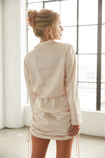 The back of this top is relaxed with long sleeves and a collar.