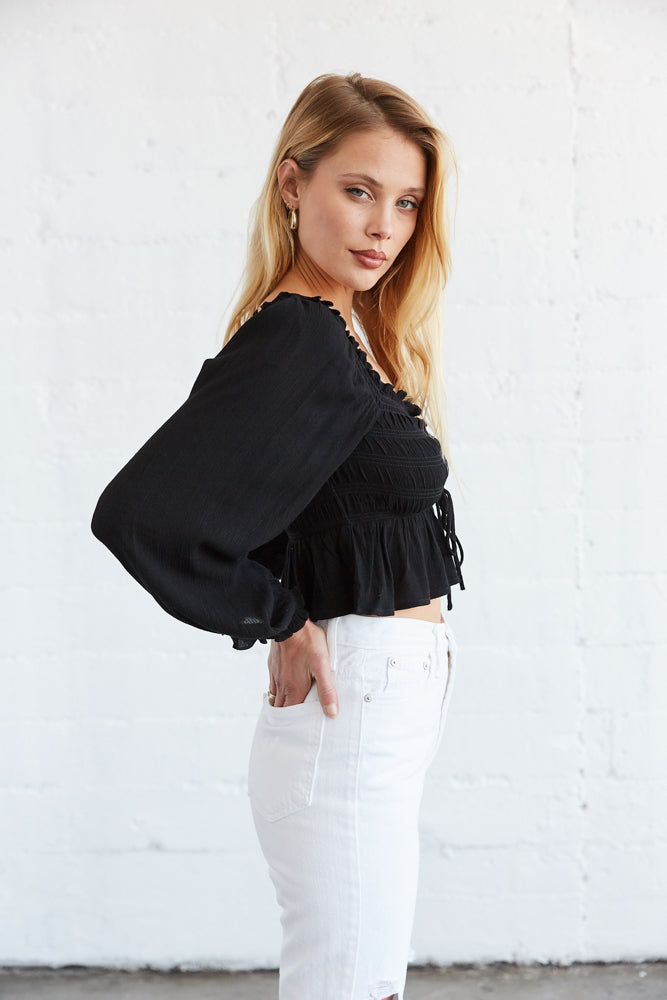 The side of this top has long billowy sleeves and elastic armholes.