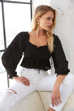 Black ruffle crop top with front tie detail.