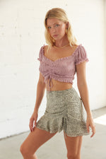This mini skirt has a ruffle trim and a high rise fit.