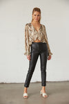 Snakeskin ruffle crop top with black leather pants.
