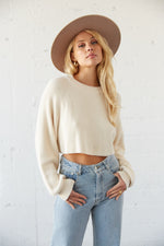 White crop knit sweater with long slouchy sleeves.
