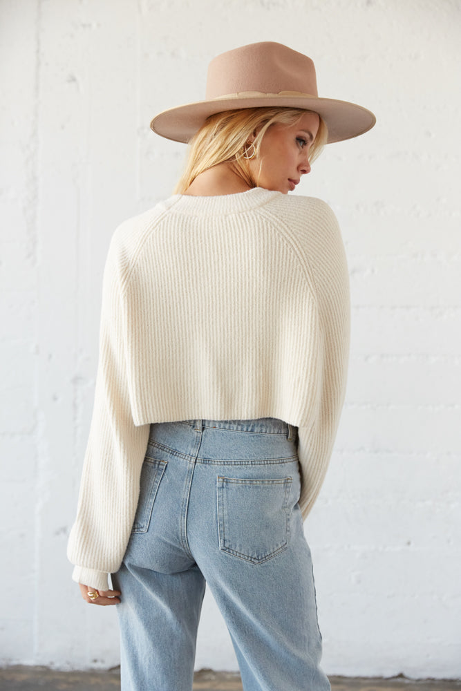 The back of this sweater is cropped with a ribbed knit design.