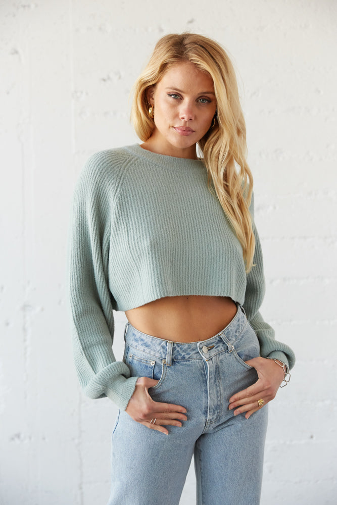 Blue crop knit sweater with long slouchy sleeves.