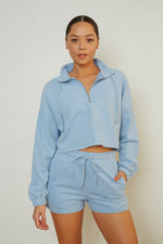Blue half zip pullover with long sleeves and matching shorts.