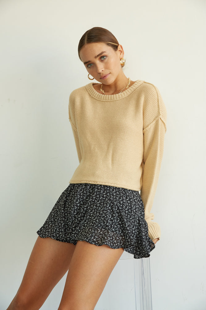 This cropped crew neck sweater is paired with black floral shorts.