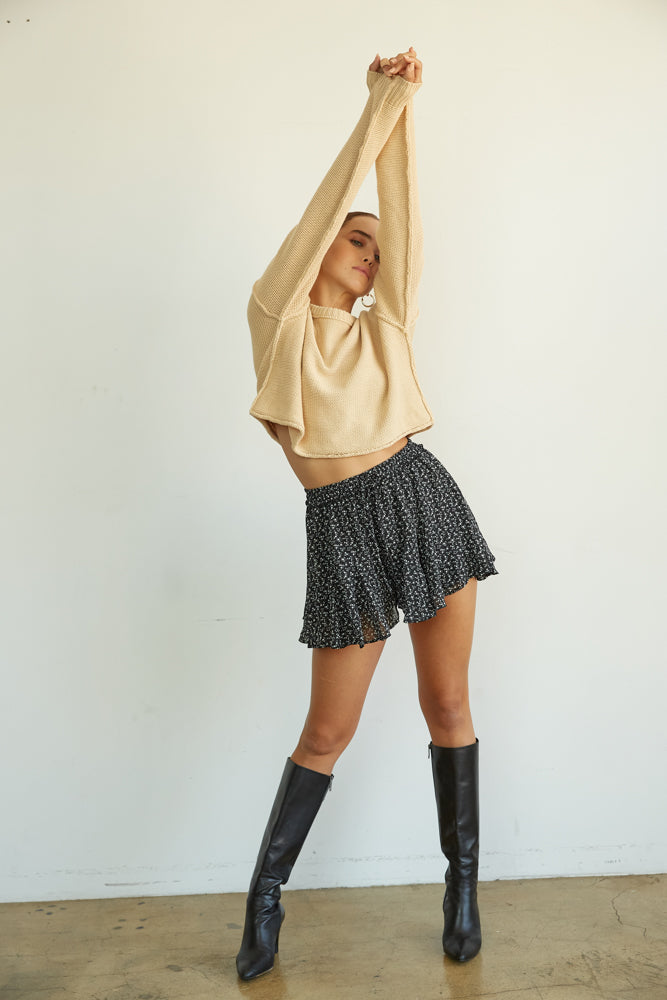 This cropped tan sweater has long sleeves and exposed seams. l
