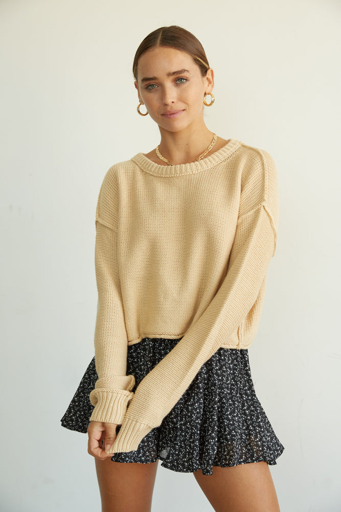 Tan knit sweater with crew neckline and exposed seams.
