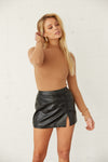 Brown long sleeve turtleneck with black leather mini skirt.