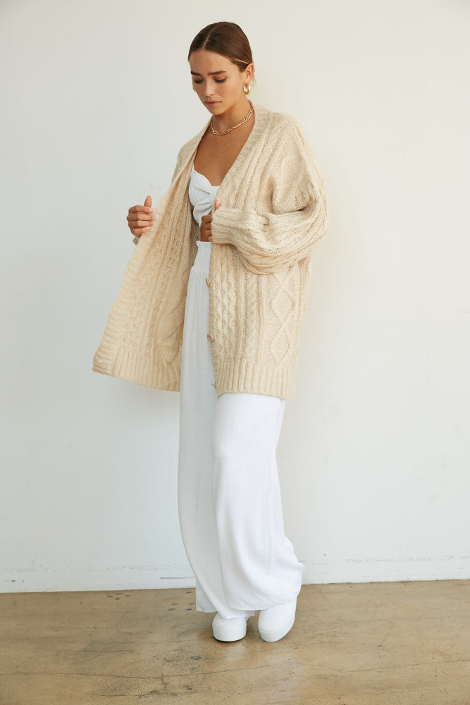 Oversized knit cardigan sweater in beige.