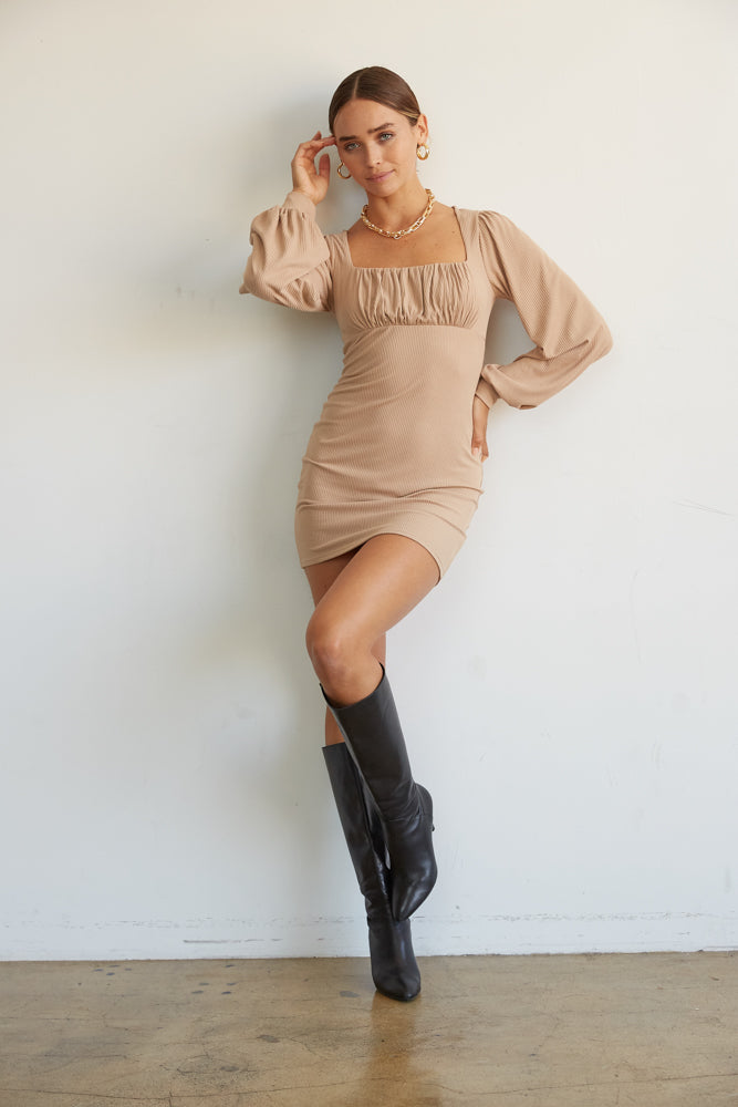 This mini dress has a square neckline and a ruched bust .