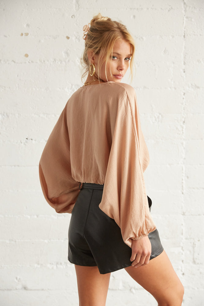 The back of this flowy top is simple and cropped.