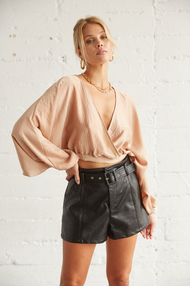 This top has long flowy sleeves and a cropped fit.