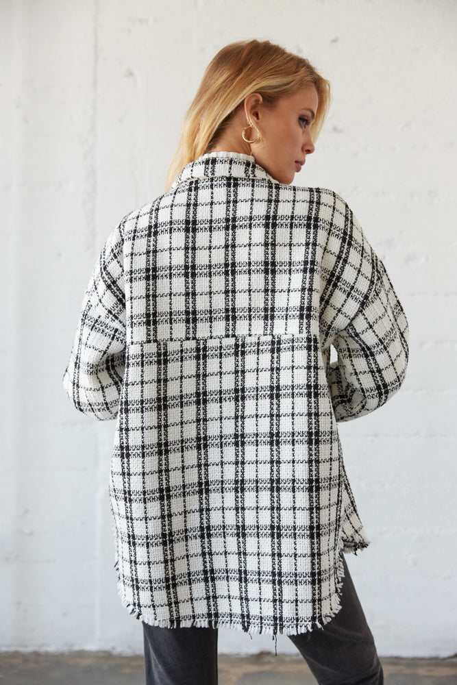The back of this flannel shirt is oversized with a frayed hem.