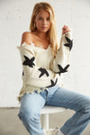 White and black star print sweater with distressed detailing.