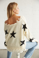 The back of this sweater has a star print design and distressed detailing on the hem.