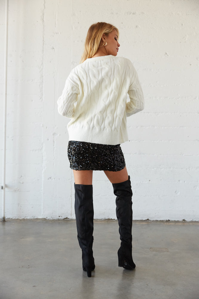 The back of this sweater is relaxed with a cable knit design.